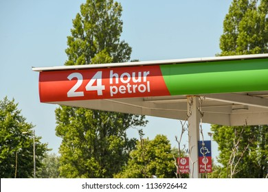 """CARDIFF, WALES - JULY 2018: """"24 hour petrol"""" sign on the canopy of a petrol station outside the Asda superstore in Leckwith in the outskirts of Cardiff."""