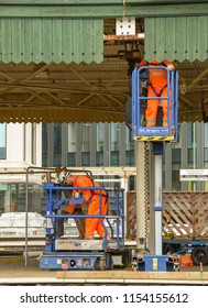 CARDIFF, WALES - JULY 2018: Workers installing fixtures for electric wires on the canopy of Cardiff Central station. It's part of the project for electrification of the London to Cardiff Railway line.