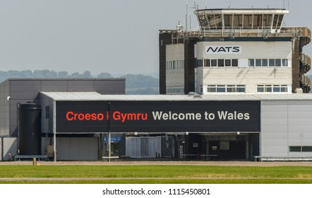 """CARDIFF, WALES - JUNE 2018: Control tower and """"Welcome to Wales"""" sign on the side of the terminal building at Cardiff Wales Airport"""