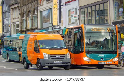 CARDIFF, WALES - MARCH 2019: Single deck bus operated by Cardiff Bus stopped at traffic lights in Cardiff city centre. Alongside it is a Cardiff Bus maintenance vehicle.