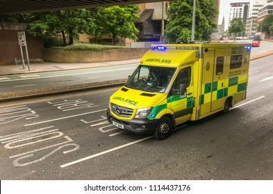 CARDIFF, WALES - MAY 2018: An ambulance driving through a city centre street on an emergency call with its blue lights flashing