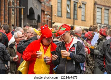 CARDIFF, WALES - NOVEMBER 2018: Two Welsh rugby supporters having a drink and talking in a crowd outside a public house in Cardiff city centre before an international rugby match.