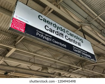 CARDIFF, WALES - OCTOBER 2018: Bilingual station name sign suspended from the platform roof at Cardiff Central railway station. The sign is sponsored by Cardiff University.