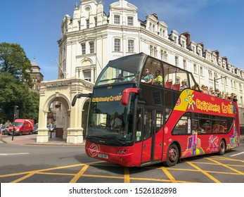 "CARDIFF, WALES - OCTOBER 2019: Sightseeing ""hop on hop off"" bus in Cardiff city centre. In the background is The Angel Hotel, a Cardiff landmark."