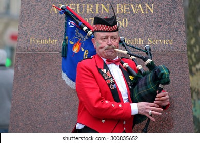 CARDIFF, WALES, UNITED KINGDOM, MArch 14th, 2015, Scottish man playing bagpipe in front of Aneurin Bevan statue from Cardiff city center, after a rugby mach between Wales and Ireland.