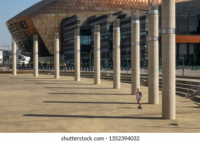 CARDIFF, WALES--MAY 19, 2018: A skateboarder glides through Roald Dahl Plass, with Wales Millennium Centre behind him. The square is named for writer Roald Dahl and featured in Dr. Who and Torchwood.