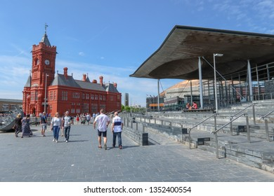 CARDIFF, WALES--MAY 20, 2018: People stroll around Cardiff Bay on a sunny day, passing landmarks like the brick Pierhead Building, Senedd Welsh Parliament, and copper-clad Wales Millennium Centre.