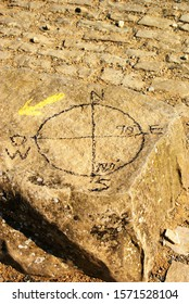 Cardinal points painted on a rock indicating with a yellow arrow the direction to follow the road to Santiago.