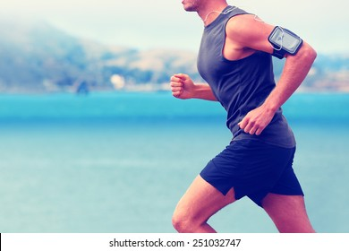 Cardio runner running listening smartphone music. Unrecognizable body jogging on ocean beach or waterfront working out with heart rate monitor app device and earphones in summer.