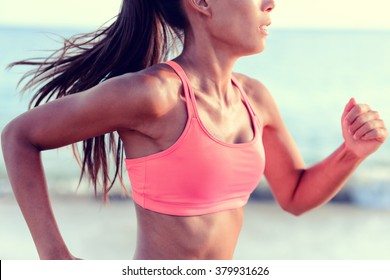 Cardio running workout - Upper body closeup crop of unrecognizable woman runner in fast motion showing pink sports bra activewear clothing in ocean beach nature background.