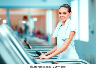 Cardio training. Side view of beautiful teen girl n in sports clothing and towel on her shoulders smiling after her workout on a treadmill in the gym