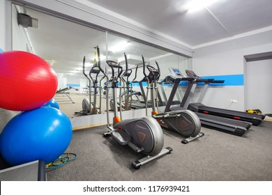 Cardio zone in modern gym. Ellipticals and treadmills.