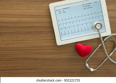 Cardiogram, ecg, electrocardiogram heart showing in tablet computer and stethoscope on desk of doctor. Concepts of cardiology and medical check up. top view.