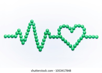 Cardiogram with heart from green pills isolated on white background.