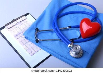 Cardiogram with medical stethoscope and red heart with doctor coat on table
