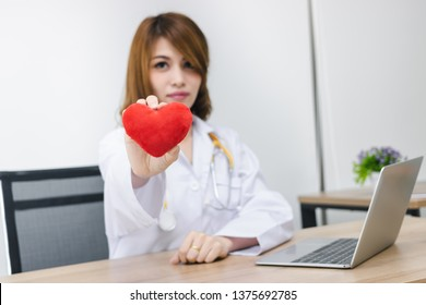 Cardiologist Asian female doctor with red heart in hands. Healthy care and medical concept. Selective focus and shallow depth of field