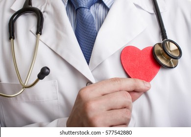 Cardiologist doctor holding heart shape with stethoscope on his neck.