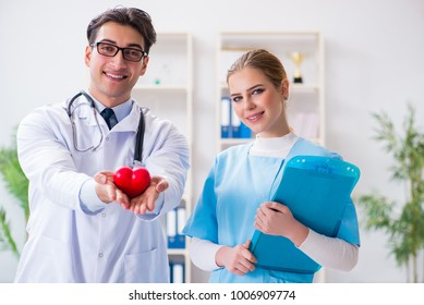 Cardiologist with his nurse assistant posing in hospital