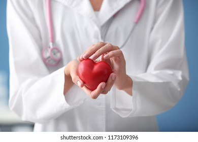 Cardiologist with red heart in clinic, closeup