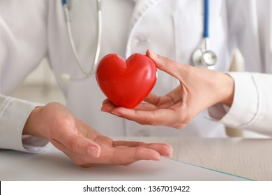 Cardiologist with red heart at table in clinic, closeup