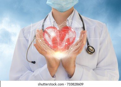 Cardiologist shows a heart in hands on sky background.