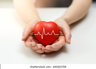 cardiology or health insurance concept - red heart in hands