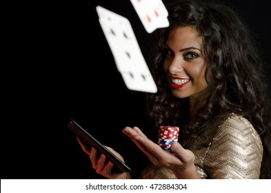 Cards flying in air, while girl holding poker chips ant tablet, black background. Online poker concept