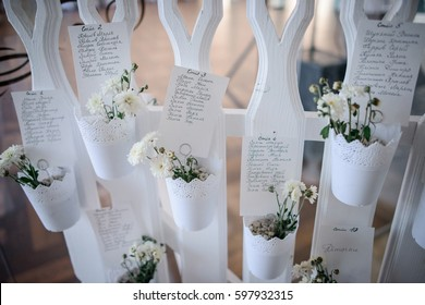 Cards with guests' names and table numbers hang on decorative white fence