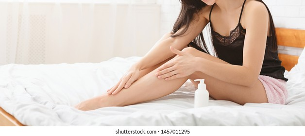 Care about female legs. Millennial woman applying moisturizing lotion on body in bed, panorama with free space