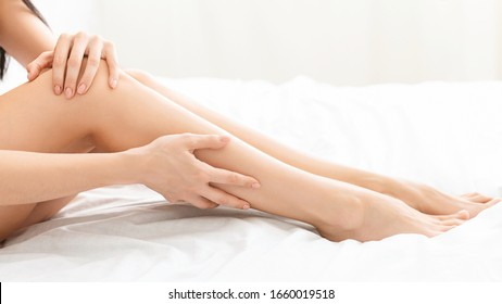Care about female legs. Young woman touching smooth skin of her legs in bed, panorama, free space