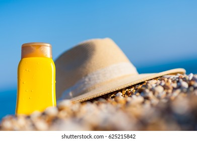 Care against the sunburn - protective sunscreen creme in yellow plastic bottle and straw hat in the beach sand with the beautiful sea in the background