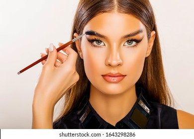 Care beauty eyebrow. Beautiful Young Woman Portrait.  Makeup Artist does Face and Eyebrow Makeup. Perfect Bushy Eyebrows. Glossy Peach Lips. Makeup. Beautiful woman with brow brush in hand.