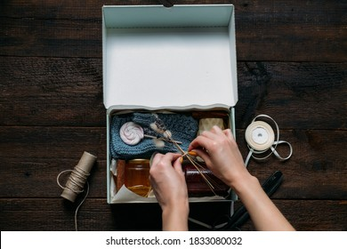 Care box, package ideas. Female hands fold a care box with sweets and warm clothes. Care Package Delivery, Fall Winter holidays Food Care gift box. Selective focus