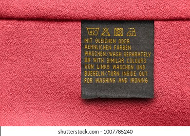 Care clothes label on english and german languages on red textile background