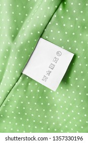 Care clothes label on green textile background