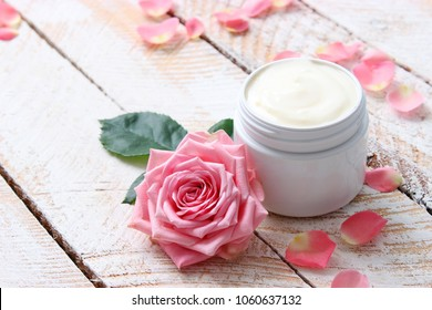 a care cream in a jar on a wooden background with beautiful roses. anti-aging cream. Cream for skin care. for hands. for face. cosmetics for care.