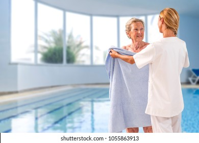 Care giver helping elderly woman to get out of swimming pool with bath towel