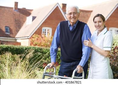 Care giver Helping Senior Man To Walk In Garden Using Walking Frame