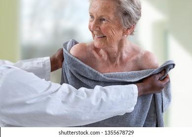 Pflegegebender oder Krankenschwester, die ältere Frauen bei der Dusche und Trocknung unterstützen