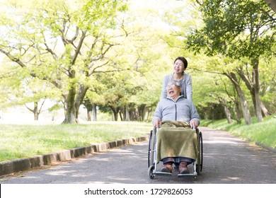 Care helper woman walking an elderly man in a wheelchair