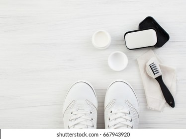 Care for leather shoes over white wooden background. The background image place for text.