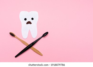 Care for the oral cavity. A startled tooth, cut out of felt with crossed toothbrushes, in the shape of a skull and bones. Flat lay. Pink background. Copy space. The concept of dental diseases.