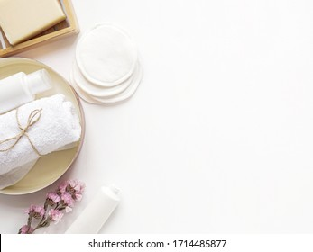care products cream, lotion, cotton pads, plant, soap, towel. bath accessories on white background, top view, copyspace. Bodycare beauty treatments at home concept, organic products, morning routine