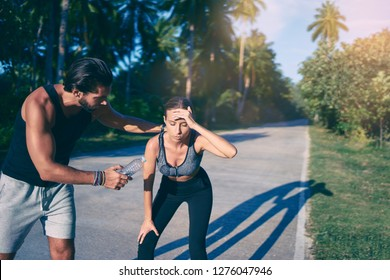 Care and support. Sport lifestyle concept. Young strong man helping his girlfriend, giving bottle of watter to tired young woman while jogging.