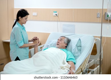 Care taker with patient. Routine health check and putting elderly patient to bed. Female nurse and care taker with senior chinese man.