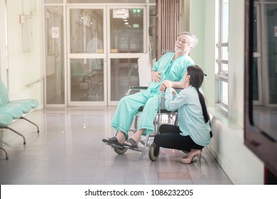 Care taker with patient. Taken care of old chinese man in wheel chair. Female nurse and care taker with senior chinese man.