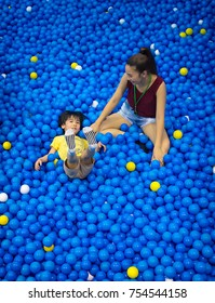 Care Taker Plays with a Boy in a Pool of Plastic Balls