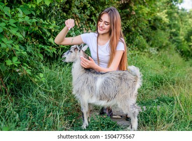 Care that matters. woman vet feeding goat. farm and farming concept. Animals are our friends. happy girl love goat. village weekend. summer. Love and protect animals. contact zoo. veterinarian goat.