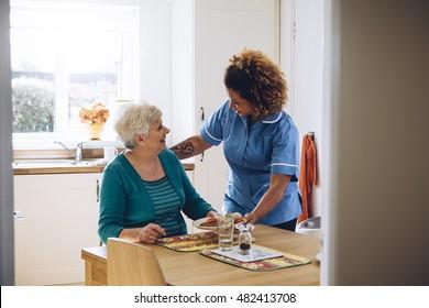 Pflegearbeiter geben einer alten Dame ihr Abendessen zu Hause.