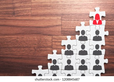 Career development and promotion concept. Business woman going and standing on height. Personal growth and development. Assembling jigsaw puzzle pieces on wood desk.